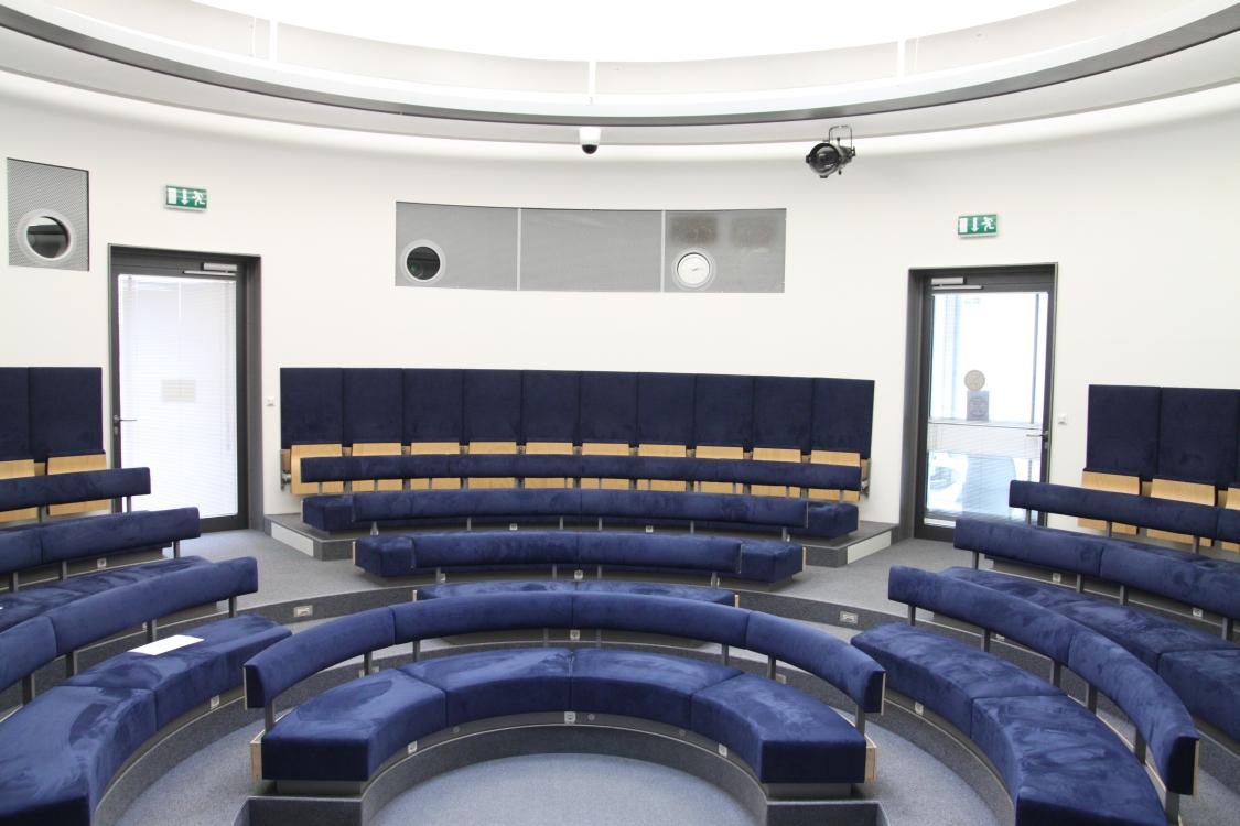 Innenansicht der Rotunde. Ein kreisförmiger, in Stufen angeordneter Raum mit festinstallierten Sitzbänken.