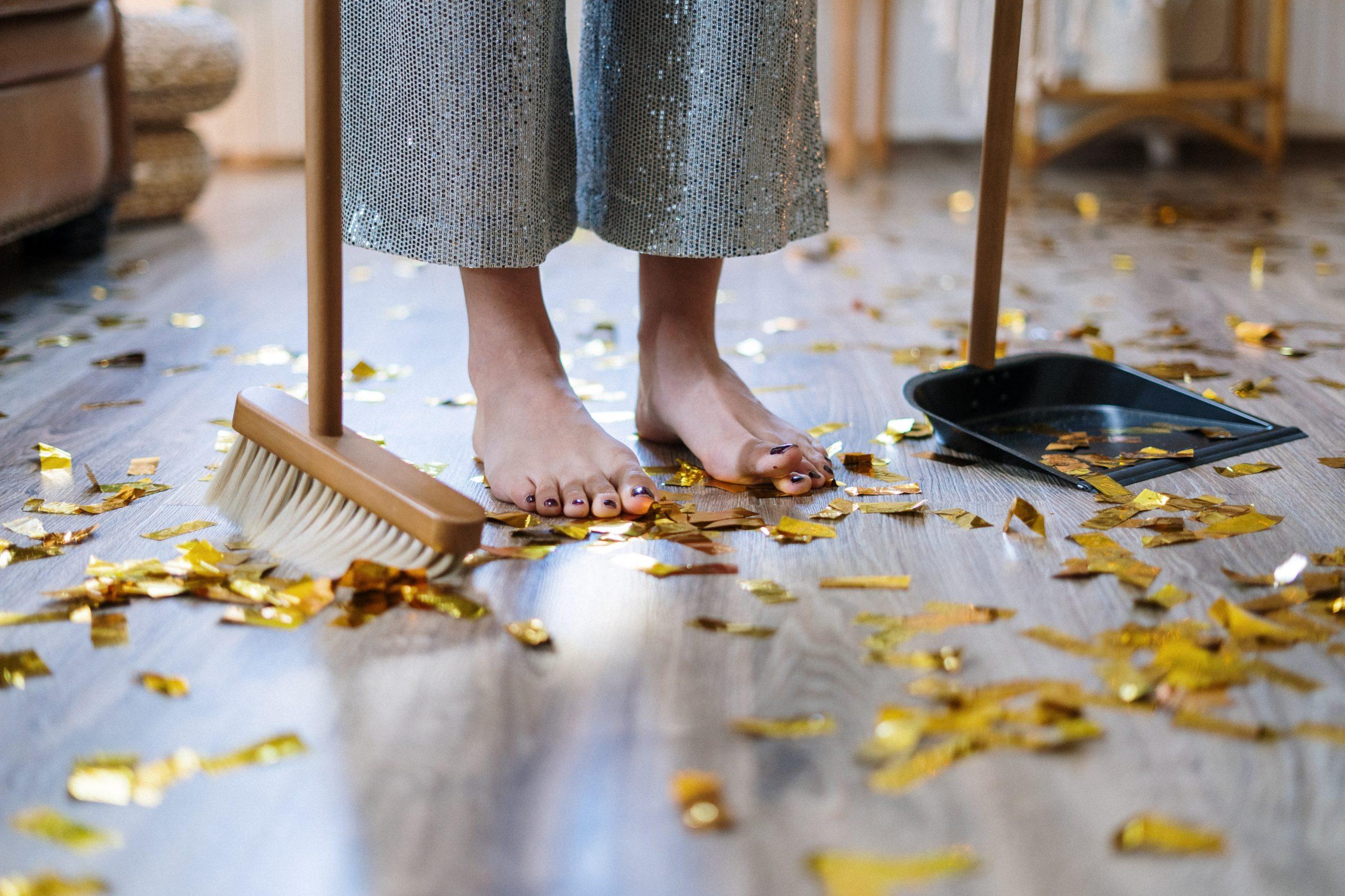 Goldglitter um Füße und Besen mit Kehrblech herum